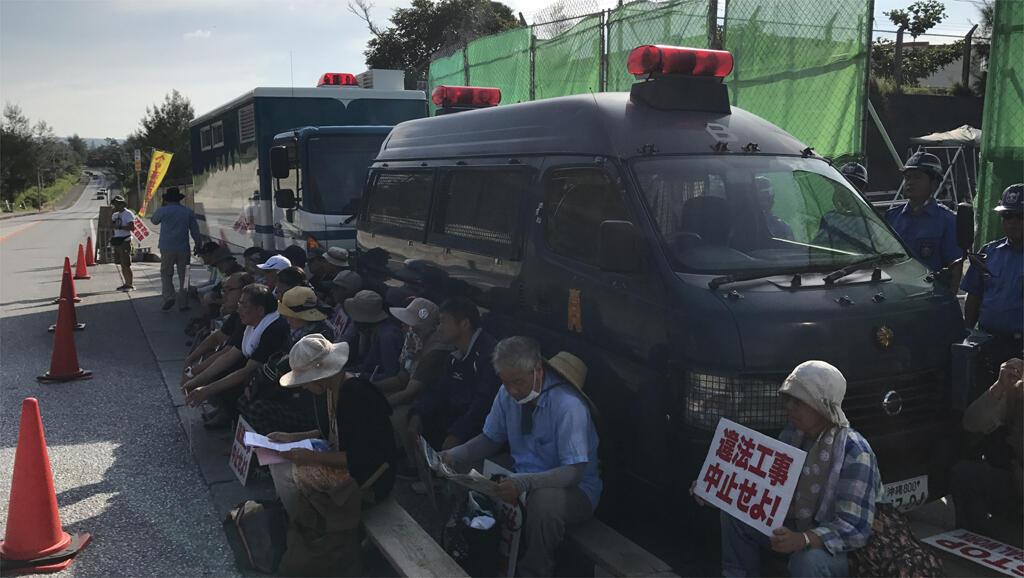 Devant le chantier de construction d'une base américaine à Okinawa.