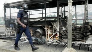 Un policier marche à côté d'un bus incendié par des manifestants pendant la campagne présidentielle en Côte d 'ivoire. Abidjan le 19 octobre 2020.