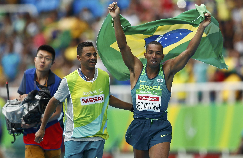 Ricardo Costa de Oliveira desfila com a bandeira do Brasil para comemorar sua medalha de ouro.