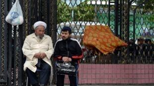 Deux hommes de la minorité musulmane ouïghours discutent dans une rue de Urumqi, la capitale du Xinjiang.