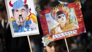 Moamer Kadhafi's opponents carry placards denouncing the Libyan leader.