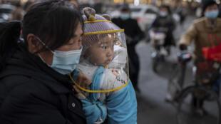 Una madre y su hijo cerca de un centro comercial en Wuhan (China) el 13 de enero de 2020