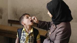 Un travailleur de santé administre le vaccin de la polio à un enfant à Alep, le 4 mai 2014
