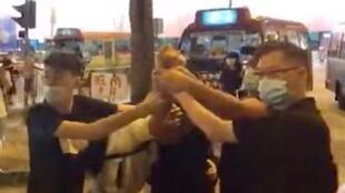 观塘区举办6.12一周年社会展览,一名男子持刀冲入人群乱砍幸被旁人制服,合力捉紧其握刀的手,涉嫌行凶者为民建联前社区主任。香港,2020年6月13日。