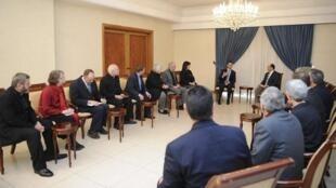 No sábado (18), al-Assad (ao fundo, à esquerda) recebeu ontem uma delegação internacional da igreja anglicana.