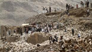 Les habitants sur les décombres de leurs maisons détruites par des frappes aériennes dans le village de Okash, près de Sanaa, la capitale du Yémen