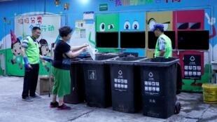 Une femme jette ses ordures dans les poubelles séparées de Shanghai, en présence de volontaires, le 2 juillet 2019.
