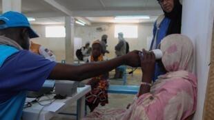 Enregistrement des empreintes oculaires d'une réfugiée malienne arrivant au camp de Mbera, le 29 mai 2019.