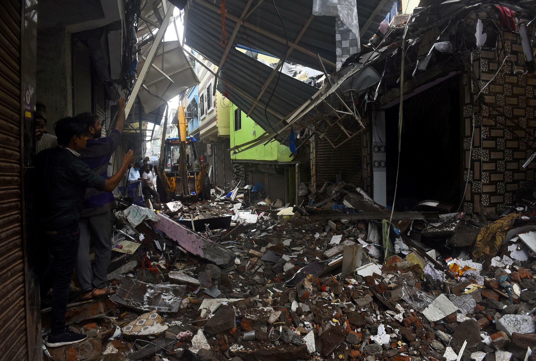 7月23日孟买一处因暴雨垮塌的房屋,左边有民众拿手机拍照