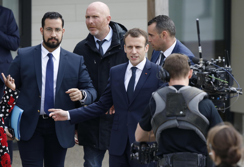 Tổng thống Pháp Emmanuel Macron bên cạnh vệ sĩ Alexandre Benalla (T) tại một trường tiểu học ở Berd'huis, tây bắc nước Pháp, để trả lời truyền hình trực tiếp về phong trào đình công.
