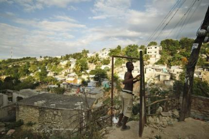 A Haitian opens the door of his destroyed house in a neighbourhood of Port-au-Prince