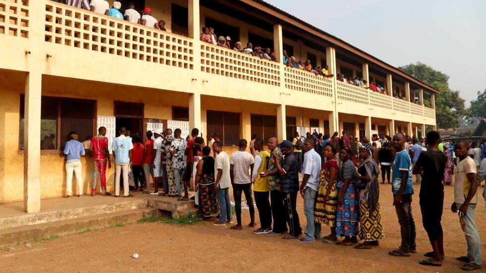 Les électeurs font la queue pour voter lors des élections présidentielles et législatives dans un bureau de vote à Petevo, 8e arrondissement de Bangui, en République centrafricaine, le 27 décembre 2020.