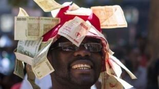 Un homme porte un chapeau décoré de chèques sans valeur, lors d'une manifestation à Harare  contre l'Etat  zimbabwéen qui veut remplacer le dollar par des coupons monétaires. Photo : août 2016.