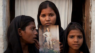 The daughters of Asia Bibi with an image of their mother outside their residence in Sheikhupura, Pakistan