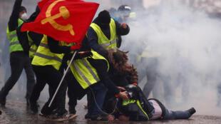 """""""Coletes amarelos"""" ajudam manifestante machucado por caminhão-tanque durante protestos no Arco do Triunfo em Paris, em 12 de janeiro de 2019."""