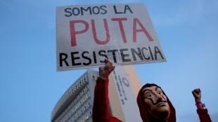 Un(e) manifestant(e) tient une pancarte «Nous sommes la putain de résistance».