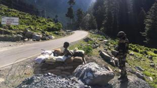 Dos miembros de las fuerzas de seguridad fronteriza indias montan guardia en una carretera que conduce a Leh, en la frontera con China, el 17 de junio de 2020 en Gagangir (India)