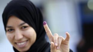 Eleitora mostra a prova de que já votou nas eleições da Tunísia.
