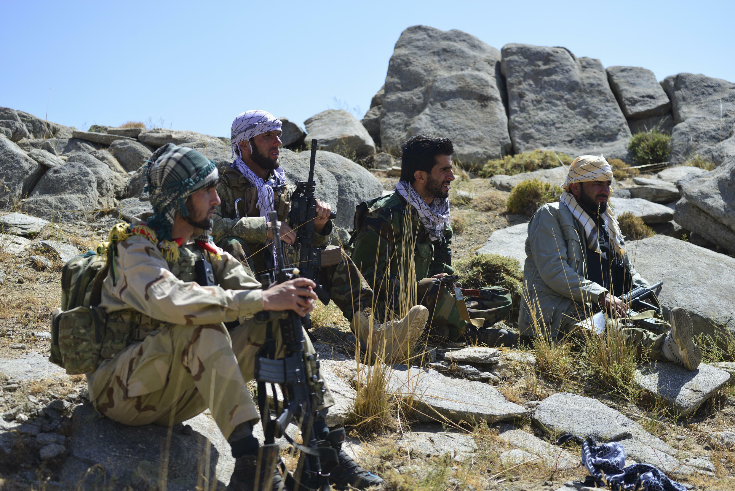 Afghan resistance movement and anti-Taliban uprising forces take rest as they patrol on a hilltop in Darband area in Anaba district, Panjshir province on September 1, 2021. - Panjshir -- famous for its natural defences never penetrated by Soviet forces or the Taliban in earlier conflicts -- remains the last major holdout of anti-Taliban forces led by Ahmad Massoud, son of the famed Mujahideen leader Ahmed Shah Massoud.