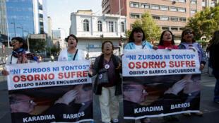 Membros do movimento Laicos de Osorno seguram cartazes com a imagem do sacerdote Fernando Karadime e do bispo Juan Barros, implicados em um escândalo de pedofilia. 16/01/18