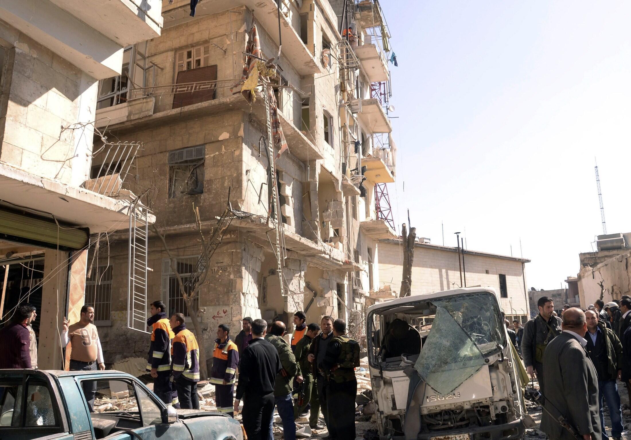 Curiosos e bombeiros observam destroços de prédio atingido por um carro-bomba na cidade de Alepo na Síria.