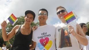 Des participants tiennent des drapeaux arc-en-ciel durant la deuxième « Viet pride » à Hanoï, le 4 août 2013.