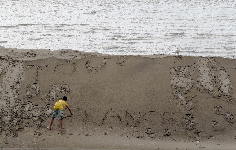 Un jeune garçon a écrit «Tour de France» sur le sable lors d'une étape de la Grande Boucle.