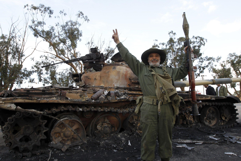 Un rebelde festeja el apoyo aliado junto a un tanque carbonizado de las fuerzas gubernamentales.