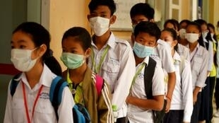Masked Cambodian students line up to disinfect their hands with an alcohol solution before entering class at a school in Phnom Penh