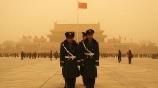 Police officers stand at Tiananmen Square during a large sand storm in Beijing