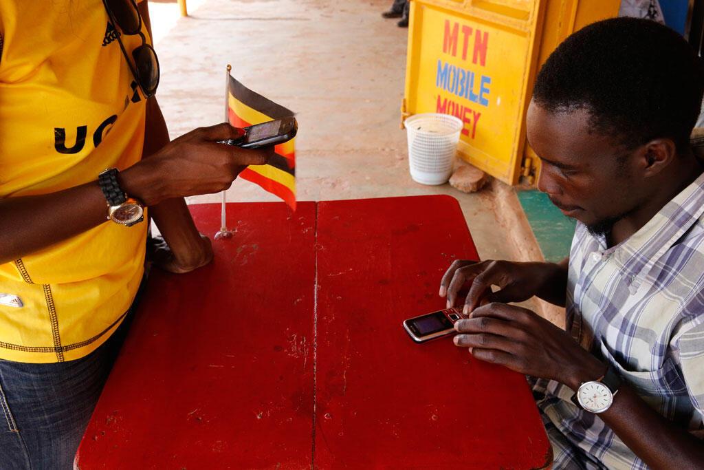 Ougandaise envoyant de l'argent avec son téléphone portable (Ouganda).