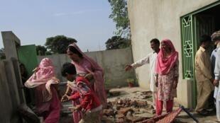 Des villageois au milieu des décombres, après des échanges de tirs entre les forces pakistanaises et indiennes, le 8 octobre 2014.