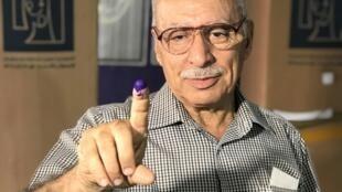 Jamil Roshdi, 70 ans, le doigt marqué par l'encre bleue, vient de voter dans le bureau de vote de l'école Dajla.