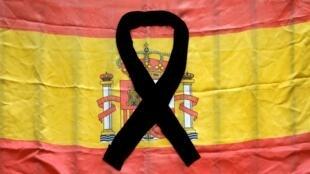 Un drapeau espagnol avec un ruban noir au balcon d'une maison confinée à Ronda, sud de l'Espagne, le 28 avril 2020.