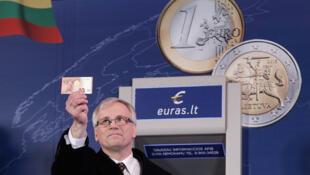 Rimantas Sadzius, Bộ trưởng Tài chính Litva giơ đồng euro vừa lấy từ máy rút tiền tự động  tại Vinius ngày 1/1/2015, một hành động biểu tượng Litva gia nhập khu vực đồgn euro.