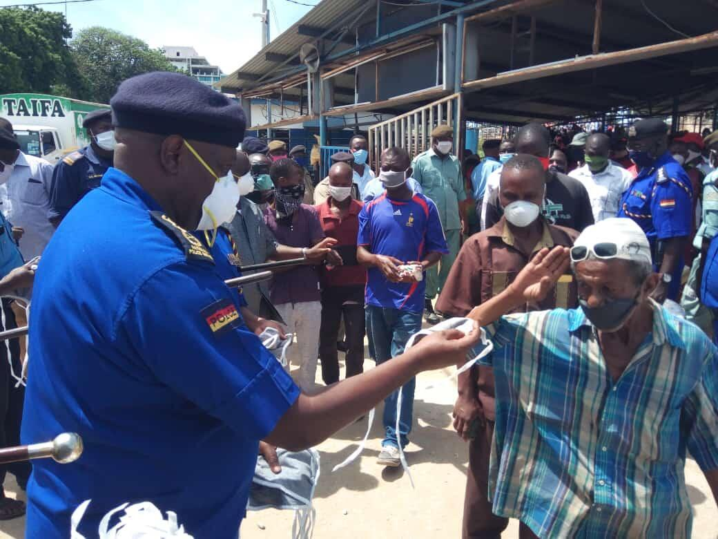 Kenya's inspector general of police aid in distributing free face masks to general public in Mombasa.