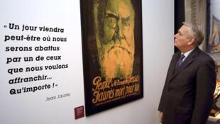 """Triển lãm về Jaurès tại Viện Lưu trữ Quốc gia. Trong ảnh, Thủ tướng Pháp Jean-Marc Ayrault. Trên tấm paneau là lời Jaurès : """"Một ngày nào đó, có thể chúng ta sẽ bị hạ gục bởi một ai đó, người mà chúng ta muốn giải phóng. Nhưng điều đó không quan trọng!"""""""