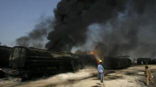 Firemen extinguish a fire on a burning oil tanker on a highway near Shikarpur