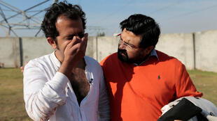 A friend comforts Pakistani journalist Taha Siddiqui after he made a statement to police in Rawalpindi