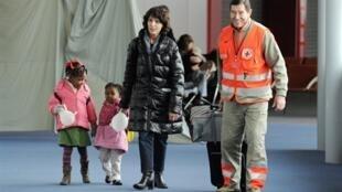 Une mère adoptive accompagnée d'enfants à sa sortie de l'aéroport de Roissy, le 22 décembre 2010.