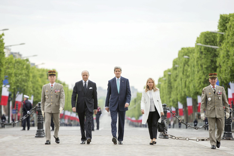 John Kerry, le chef de la diplomatie américaine et Laurent Fabius, le ministre des Affaires étrangères français ainsi que Jane Hartley, l'ambassadrice des Etats-Unis en France, sur la tombe du soldat inconnu, aux Champs Elysées, Paris, le 8 mai 2015.