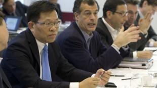 O CEO francês do Club Med, Henri Giscard d'Estaing (2° à esquerda), e o chinês Qian Jiannong (esq.), presidente do grupo Fosun Turismo, em Paris, no dia 19 de dezembro de 2014.