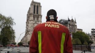Un pompier parisien face à la cathédrale Notre-Dame de Paris, ce 16 avril au matin.