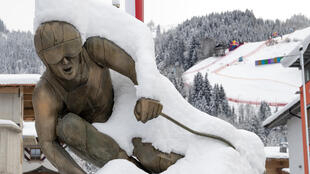 The Streif, downhill slope of the famed Hahnenkamm race, is seen behind the snow-covered statue of a skier in Kitzbuehel, Austria
