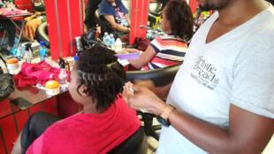 Confection de dreadlocks dans un salon de coiffure à Johannesburg (Afrique du Sud).