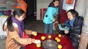 Foto tirada do blog da associação Xiaoxing que ajuda crianças que vivem sozinhas em áreas rurais. A mãe (à direita), o ex-trabalhadora migrante na cidade, decidiu voltar para casa para garantir a escolaridade de suas filhas.