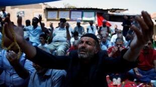 Des Palestiniens prient dans la rue devant la maison des Shamasneh, le 11 août, pour soutenir la famille dans le quartier de Sheikh Jarrah à Jérusalem-Est.