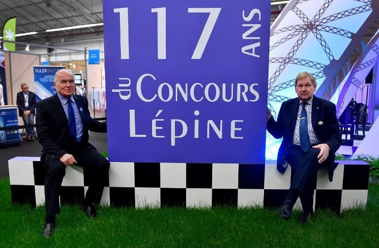 Rene-Georges Lavergne (G) président de jury du Concours Lépine et Gérard Dorey, président du Concours Lépine devant l'affiche de la 117e édition du concours, le 3 mai 2018, à la Foire de Paris.