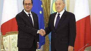 French President Francois Hollande (L) shakes hands with Kazakh counterpart Nursultan Nazarbayev in Astana