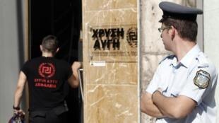 Un policier grec devant le quartier général du parti d'extrême droite Aube dorée.